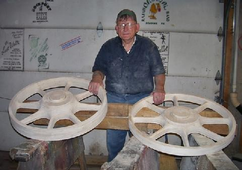 Volunteer woodworker, Bernie Perch poses with his hand-crafted patterns for No. 11's driving wheels.