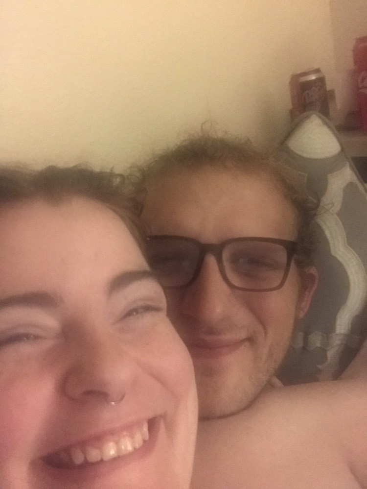A selfie of Sugar and Em, two white queers, smiling in bed. Sugar lays back across Em and smiles broadly with their teeth showing, their red hair pulled back in a bun. Em wears black-framed glasses and smiles with her mouth closed, her blonde curls mussed